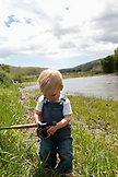 USA, Wyoming, Encampment, a young boy plays with a fly fishing rod on the bank of the North Platte river, Abara Ranch