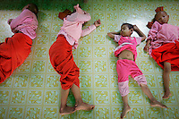 Girls sleep at a nunnery where orphans became Buddhist novice nuns after being abandoned by their parents in suburbs of Yangon April 14, 2012. British Prime Minister David Cameron and Myanmar opposition leader Aung San Suu Kyi gave powerful backing on Friday for suspending sanctions on the country, a stark shift in stance and a boon for a pariah state eager to come in from the cold.   REUTERS/Damir Sagolj (MYANMAR)