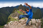A tourist visits the ancient Inca ruins of Machu Picchu, Peru.
