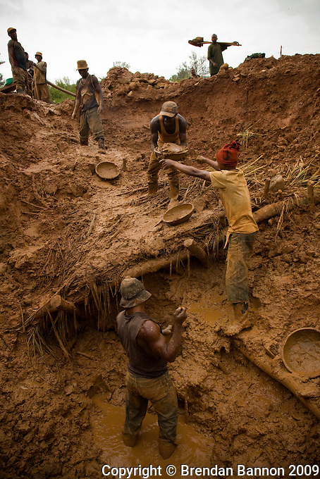 "Congolese miner Bevins in a blue shirt and hat digs in the bottom of a pit mine. "" It was only fate that brought us here  6 weeks ago. Others have  dug here before. There is no reason why we chose theis place. We are lucky here, the work is hard, but we have found  good gold and  the price is higher  here now."".Artisanal  Miners sift through the  tailings in the shadow of  an abandoned processing  plant in Kanga, outside Mongbwalu, north-eastern DRC..The tailings are bits of stone and silt left over from the refinery process. This processing plant was  the central refinery for gold found in Ituri province. Even during  the war it was pushing out 10-20 kilos of gold per month. .The shell of the buildings and the waste left behind are all that remain the company fled during the war. Since being abandoned in 2001 anything that could be carried away and used elsewhere or sold as scrap has disappeared.."