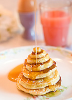 Pancakes stacked in different sizes to make a piramid, maple syrup pouring on top of it with juice and egg in background