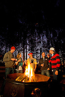 Visitors (these are models) gather around a camp fire as part of the Micro Brews Cruise outing at the US National Whitewater Center in Charlotte, NC. The USNWC, an ultimate adventure playground for outdoor enthusiasts, offers both water and land sports. Micro Brews Cruise offers flatwater kayaking, fireside dinner and craft beer tastings,
