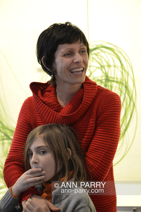 """Roslyn, New York, USA. January 31, 2015. At Artists Reception for """"The Alchemists"""" is artist Karine Falleni (wearing red sweater) exhibiting work documenting movement, including installation with green automotie tape, at Bryant Library. Curated by Ellen Hallie Schiff."""