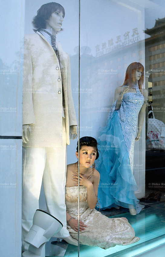China. Province of Beijing. Beijing. A young woman dressed in fancy and fashionable clothes stands among dummies in a shop window.  © 2004 Didier Ruef