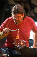 Master glass artist,forming a handle of molten glass onto a glass pitcher, Glass Studio at the Wheaton Arts and Cultural Center, Millville, New Jersey