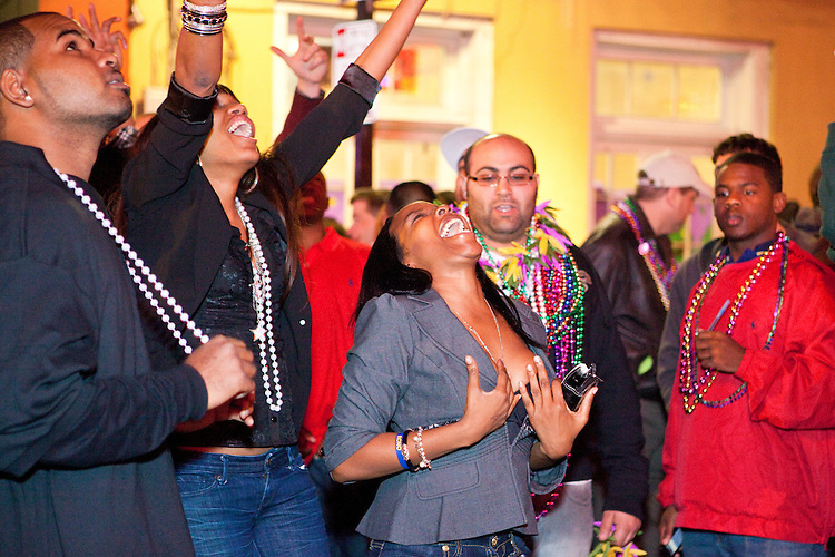 Revelers enjoy Bourbon Street and try to get beads thrown from balconies above however they can during Mardi Gras in New Orleans on February 14, 2010.