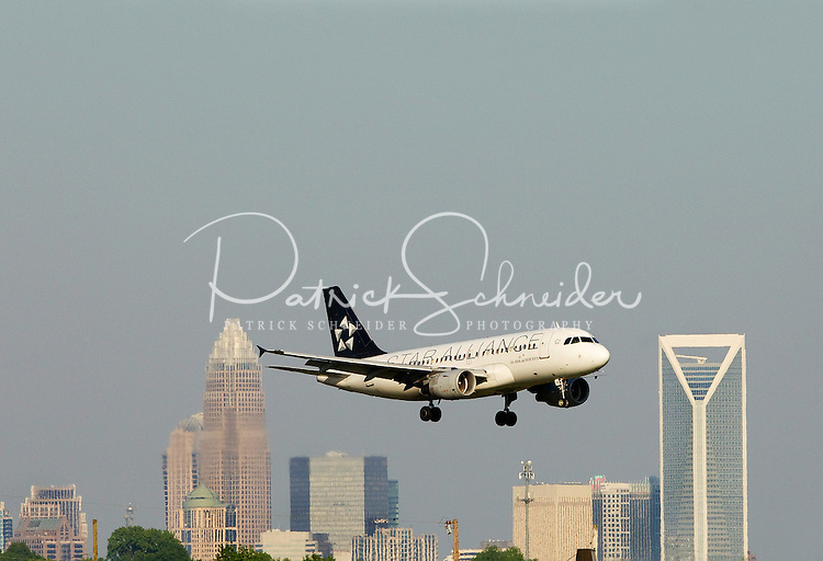 A plane makes its descent at Charlotte-Douglas International Airport in Charlotte, North Carolina. The downtown Charlotte skyline is in the background. Charlotte-based photographer has other images of transportation, airplanes on runways (and taking off and landing) and interior/exterior airport images of Charlotte-Douglas Intl Airport in portfolio.