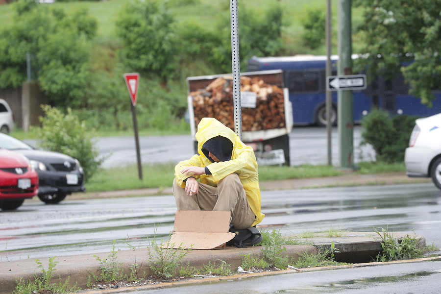 Homeless person begs on the street corner in the rain. Photo/Andrew Shurtleff Photography, LLC