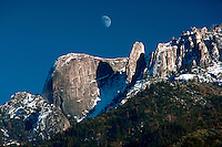 """Sequoia National Park in winter. The """"Castle Rocks"""" and quarter moon over them in blue sky. California"""