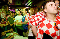 Croatia fan Sinisa Lukic tries to get a better view of the action during his team's match against Brazil on June 13, 2006 at the Scorpio Bar in New York City.<br /> <br /> The World Cup, held every four years in different locales, is the world's pre-eminent sports tournament in the world's most popular sport, soccer (or football, as most of the world calls it).  Qualification for the World Cup is open to any country with a national team accredited by FIFA, world soccer's governing body. The first World Cup, organized by FIFA in response to the popularity of the first Olympic Games' soccer tournaments, was held in 1930 in Uruguay and was participated in by 13 nations.    <br /> <br /> As of 2010 there are 208 such teams.  The final field of the World Cup is narrowed down to 32 national teams in the three years preceding the tournament, with each region of the world allotted a specific number of spots.  <br /> <br /> The World Cup is the most widely regularly watched event in the world, with soccer teams being a source of national pride.  In most nations, the whole country is at a standstill when their team is playing in the tournament, everyone's eyes glued to their televisions or their ears to the radio, to see if their team will prevail.  While the United States in general is a conspicuous exception to the grip of World Cup fever there is one city that is a rather large exception to that rule.  In New York City, the most diverse city in a nation of immigrants, the melting pot that is America is on full display as fans of all nations gather in all possible venues to watch their teams and celebrate where they have come from.