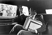With an arm-load of papers and documents, United States President Gerald R. Ford has a morning smile and a wave for people seeing him pass in his car en route to his office at the White House on August 11, 1974.  At the time this photo was taken, President Ford had not taken up residence in the White House, but was still living at his Alexandria, Virginia residence.<br /> Mandatory Credit: David Hume Kennerly / White House via CNP