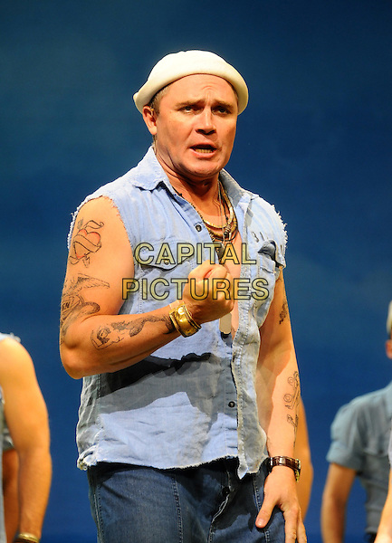 Alex Ferns on stage at 'South Pacific' photocall held at the Barbican Centre,.London, England..August 22nd, 2011.stage play half length blue denim sleeveless shirt tattoos white hat fist.CAP/CJ.©Chris Joseph/Capital Pictures.