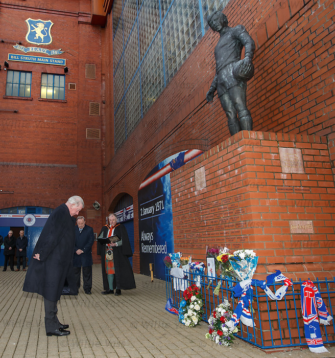 John Greig pays his respects to the supporters who never came back home at the memorial statue at Ibrox Stadium