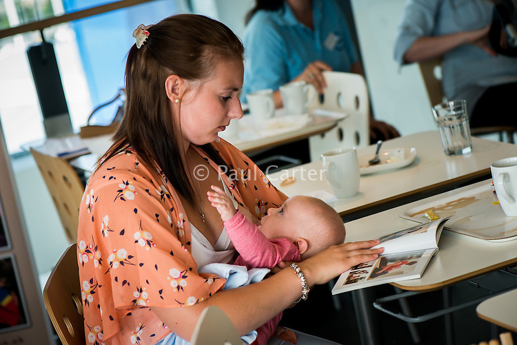 A mother breastfeeds her baby while reading at a book at a  breastfeeding support group who are meeting up in the restaurant of a local super store to celebrate WABA World Breastfeeding Week and to enjoy talking together.<br /> <br /> Image from the breastfeeding collection of the &quot;We Do It In Public&quot; documentary photography picture library project: <br />  www.breastfeedinginpublic.co.uk<br /> <br /> Hampshire, England, UK<br /> 07/08/2013<br /> <br /> &copy; Paul Carter / wdiip.co.uk