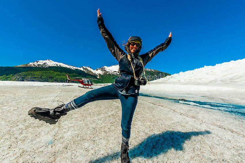 Woman enjoys landing on the Mendenhall Glacier by helicopter, near Juneau, Alaska USA.
