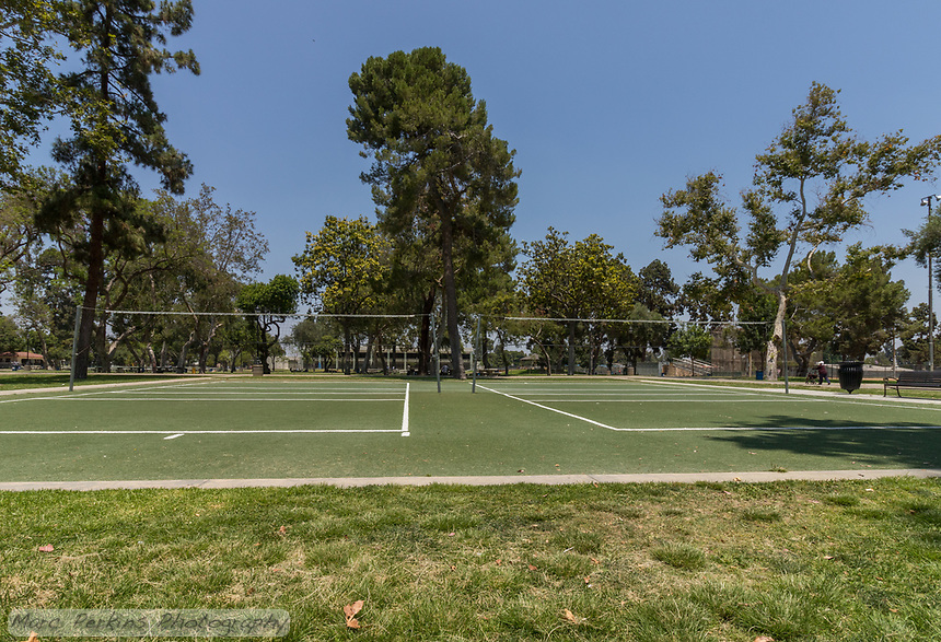 The artificial turf volleyball courts at South Gate Park, seen with a wide-angle low perspective.  An older woman pushing a walker strolls past in the distance, and the mature trees of the park tower overhead.