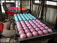 BNPS.co.uk (01202 558833)<br /> Pic: PhilYeomans/BNPS<br /> <br /> The cloth 'eights' are then glued and heat molded on to the rubber ball.<br /> <br /> Smashed it - The last tennis ball maker in the Western world is bouncing back...<br /> <br /> Louise Price of tennis ball maker Price of Bath is leading the family business's fight back against far eastern competition than nearly wiped out the company a few decades ago.<br /> <br /> And the company is now doing so well again that it will soon be moving to brand new larger factory in Box in Wiltshire.<br /> <br /> Price of Bath was set up by her grandfather Joseph in the 1930's and after WW2 employed 120 people churning out 84,000 balls a week - nowadays it's the last tennis ball maker in the western world, and produces a much more modest 6000 balls a week from raw rubber from Malaysia to finished product.<br /> <br /> Louise's father Derek, who invented the rubber tiles used on nuclear powered submarines as well as running the family business, still works full time in the dickensian factory at the age of 88.