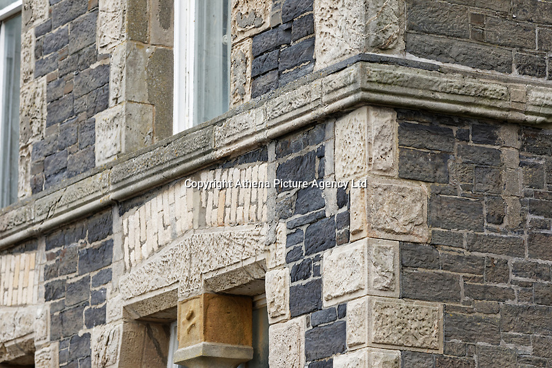Pictured: Detial of the front of the old Police Station in Aberystwyth, Wales, UK. Wednesday 28 August 2019<br /> Re: Opened 1866, built by the Hafod Hotel Co as the Queens Hotel; architects, Hayward and Davies; builder George Lumley of Aberystwyth. Sold in 1877 and later converted to local government use; remodelled in1950 by G R Bruce, County Architect.<br /> Detached towards N end of the Promenade, with main entrance to side elevation in Albert Place and rear elevation to Queens Road.<br /> Hotel de Ville style. Asymmetrical 3-storey attic and basement snecked rubble 13-bay W (Promenade) elevation; stepped front with mostly vermiculated dressings, stock brick voussoirs, deep entablature and cornice and cill bands; buttresses to ground floor centre. Steep pitch mansard slate roof with truncated chimney stacks. Dormers with steep overhanging roofs and casement windows; paired to left. 3-bays advanced near the right hand end and with additional storey and splayed angles to 2nd floor (with small cast-iron parapets) and 3rd floor; also to top floor) with small cast-iron parapets) and 3rd floor; also to top floor at the corner. Sash windows, some paired; anthemion panelled cast-iron window box holder across central bays.