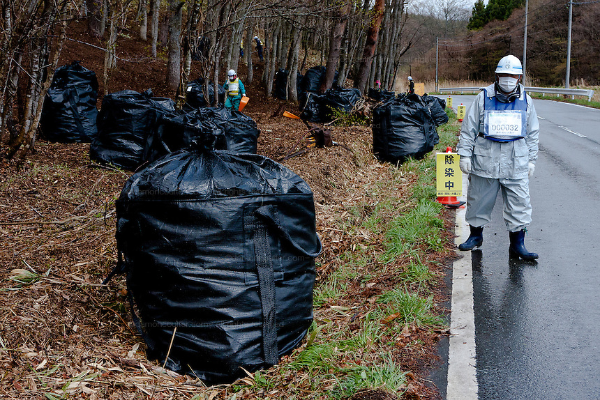 Workmen remove undergrowth and topsoil along a road near Katsurao in rural Fukushima, Japan, Wednesday May 1st 2013.  The Japanese government has decided to remove the topsoil and vegetation from the areas affected by radiation after the disaster at Fukushima Daichi nuclear plant on March 11th 2011