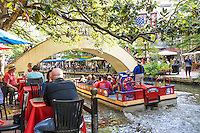This is another image of the water side dinning along the river walk as a tour boat goes under one of the pedestrian bridge in downtown San Antonio.