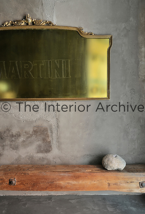 A gilt-framed mirror etched with the word Martini hangs on a grey stone wall above and rough wooden beam shelf.
