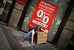 A man holding a cardboard reading ''help me, I am hungry'' asks for money in front of a bank in Madrid, on Juny 9, 2012. Spain has not changed its position and is not seeking aid for its banking sector, an economy ministry spokeswoman said on June 9 ahead of a conference call by eurozone finance ministers. (c) Pedro ARMESTRE