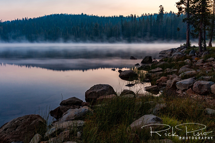 A shallow layer of fog hangs over Juniper Lake at dawn in Lassen Volcanic National Park