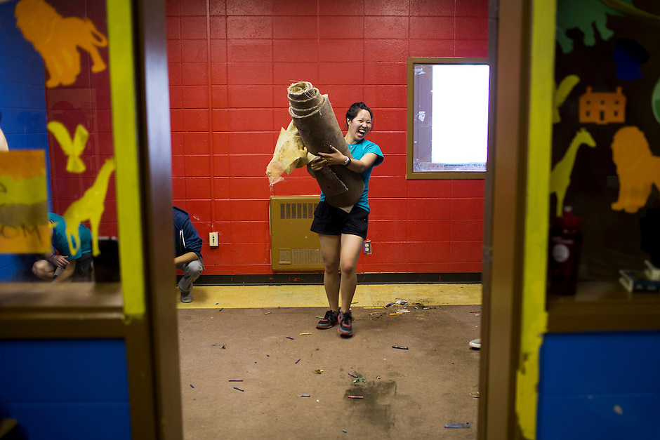 "Josephine Lukito reacts as she removes carpeting during ""Circle the City with Service,"" the Kiwanis Circle K International's 2015 Large Scale Service Project, on Wednesday, June 24, 2015, at the Friendship Westside Center for Excellence in Indianapolis. (Photo by James Brosher)"