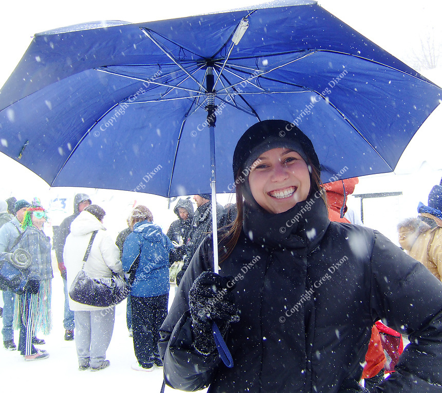 Kristin Kosmin decides that a down coat and umbrella are a smart way to watch the Polar Plunge at Olin Park on Saturday in Madison