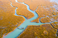 TA fishing boat lies in a colourful small river that has formed in the lower reaches of the Yellow River estuary which marks the southernmost boundary of Bohai Bay. Shandong province, China. 2019