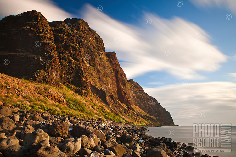 Kauai's Na Pali coast at sunset seen under long exposure to blur cloud movement