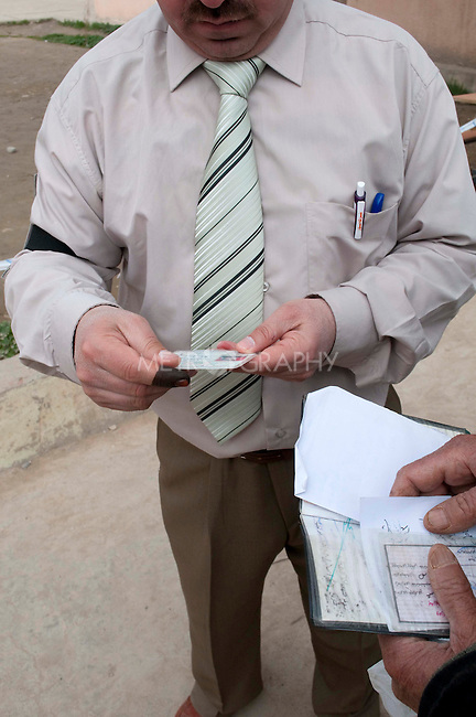 KIRKUK, IRAQ: An election official checks voters' IDs outside a polling station...Residents of the city of Kirkuk vote for the first time.  Because of violence in the ethnically mixed city, Kirkuk was excluded from the 2005 elections...Photo by Kamaran Najm/Metrography