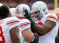 Ohio State Buckeyes offensive lineman Pat Elflein (65) is grabbed by in Ohio State Buckeyes offensive lineman Darryl Baldwin (76) before the first quarter of their game against the University of Maryland Terrapins at Byrd Stadium in College Park, Maryland on October 4, 2014. (Columbus Dispatch photo by Brooke LaValley)