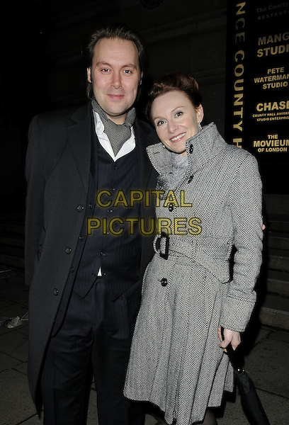 CHRISTIAN & EMILY McKAY.The London Evening Standard British Film Awards 2010, The Movieum of London, County Hall, London, England..February 8th 2010.half 3/4 length grey gray jacket coat blue suit married husband wife herringbone waistcoat umbrella  .CAP/CAN.©Can Nguyen/Capital Pictures.