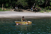 Anse Chastanet Bay, St. Lucia. Local man with dreadlocks paddling yellow, green and red boat with beach and trees behind.