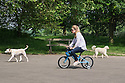 A woman rides her small daughter's bicycle, in the sunshine, on the Bank Holiday weekend, in Regent's Park.