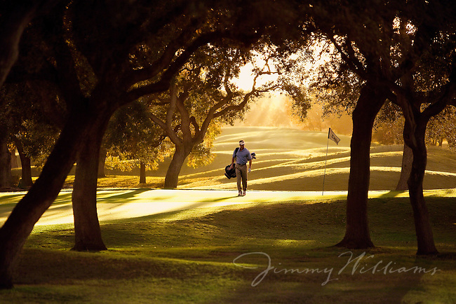 A golfer walks through a golf course to his next shot.