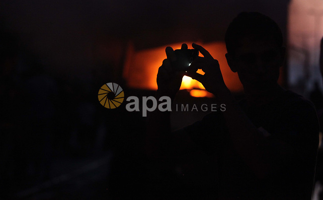 A Palestinian man records video by his mobile as firefighters try to extinguish fire from  soap factory that caught fire moments after it was hit by an Israeli airstrike in Gaza City August 10, 2014. Palestinian and Israeli negotiators on Sunday said they had accepted an Egyptian proposal for a new 72-hour truce with Israel, clearing the way for a possible resumption of talks on a long-term cease-fire arrangement in the Gaza Strip. Photo by Ashraf Amra
