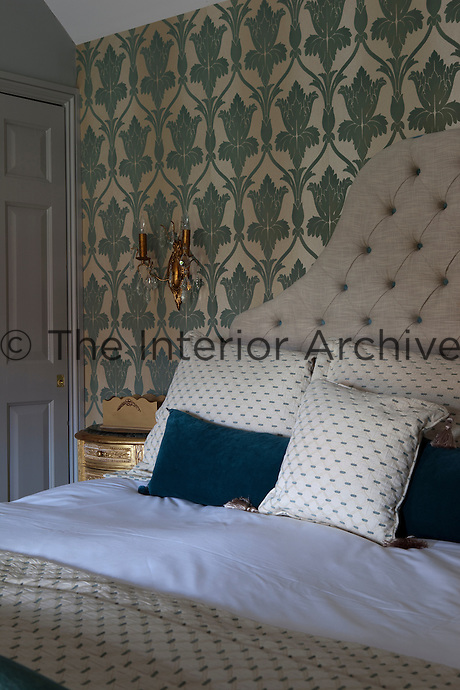 A comfortable double bed with an upholstered headboard in a bedroom with green patterned wallpaper