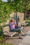 Two women sitting on a bench on Shrewsbury Street in Worcester, MA talking