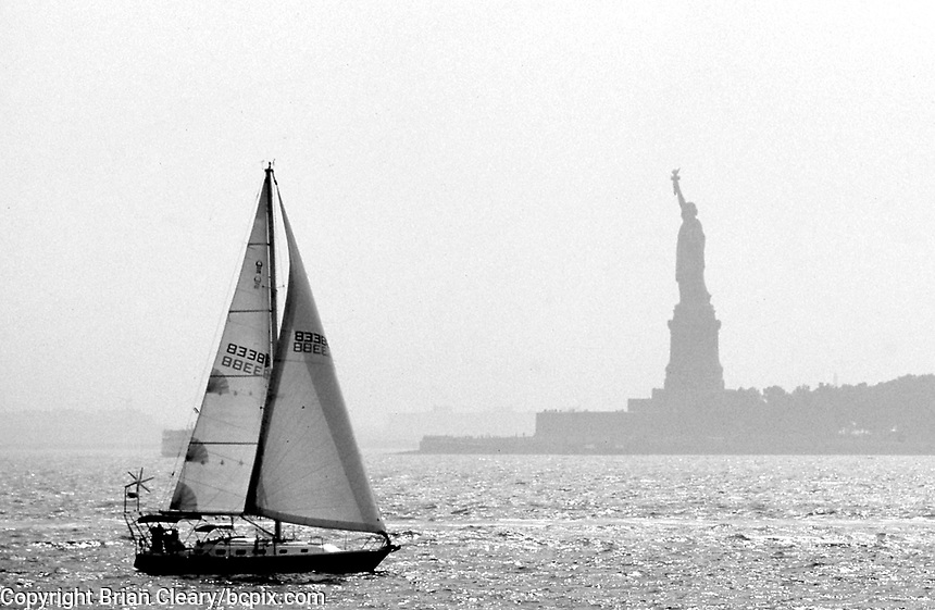 Sailboat, Statue of Liberty in New York City Harbor,  New York City.  (Photo by Brian Cleary/www.bcpix.com)