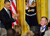 """United States President Barack Obama and first lady Michelle Obama present the 2010 Medal of Freedom, """"the Nation's highest civilian honor presented to individuals who have made especially meritorious contributions to the security or national interests of the United States, to world peace, or to cultural or other significant public or private endeavors"""", to former U.S. President George H.W. Bush in a ceremony in the East Room of the White House in Washington, D.C. on Tuesday, February 15, 2011..Credit: Ron Sachs / CNP"""