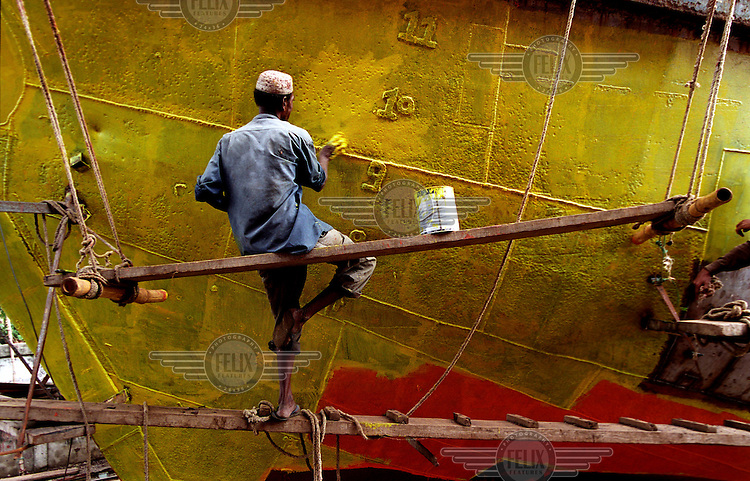 Labourers on a ship construction site complete the hull of a