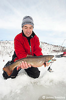 Angler holding up a winter brook trout caught ice fishing.