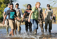 NWA Democrat-Gazette/DAVID GOTTSCHALK  Jane Maginot, with the Washington County Extension Service, helps carry a kick and pick net with Fayetteville High School students in the Outdoor Education Class Wednesday, September 16, 2015 in Clear Creek in Johnson. The class, taught by Laura Ring, was assessing the water quality based on the biodiversity benthic organisms.