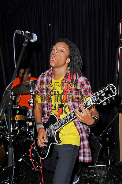 Dee Radke of Radkey <br /> performing in concert, The Blackeart, Camden, London, England. <br /> 17th October 2013<br /> on stage in concert live gig performance performing music half length red check shirt yellow top guitar mouth open <br /> CAP/MAR<br /> &copy; Martin Harris/Capital Pictures