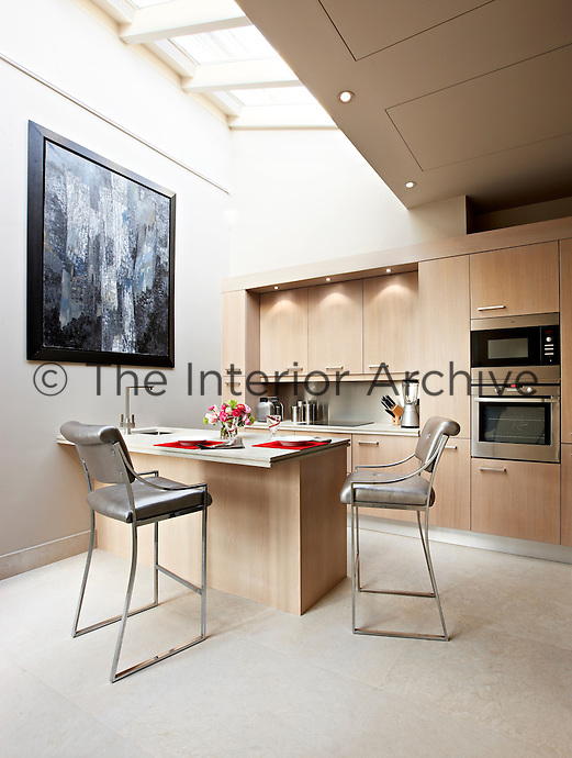 Designer stools and a specially designed kitchen island provide a place for eating under the skylight in this chic kitchen