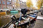 A Dutch man cleans the water out of his small boat on the canals of Amsterdam, the Netherlands.