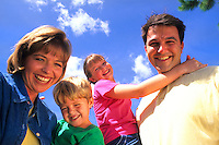 Young affluent family spending quality time together at a local park portrait from below
