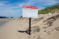 A sign provides information about damage and repairs to the parking lot after storms earlier this year at Herring Cove Beach in the Cape Cod National Seashore outside of Provincetown, Mass., USA, seen on Fri., July 1, 2016.